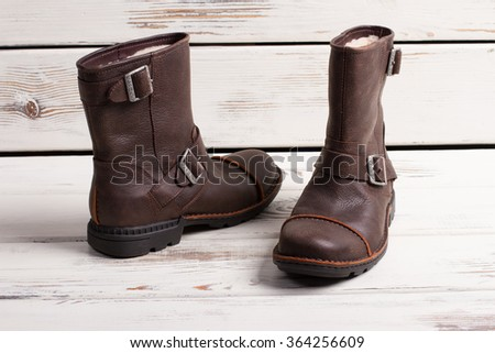 Stylish shoes. Beautiful pair of men's winter boots on a wooden board. - stock photo