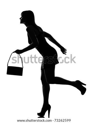 stylish silhouette caucasian beautiful woman running holding purse full length on studio isolated white background - stock photo