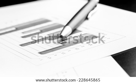 Stylish silver ballpoint pen lying on a bar graph at an oblique angle in a business analysis concept.