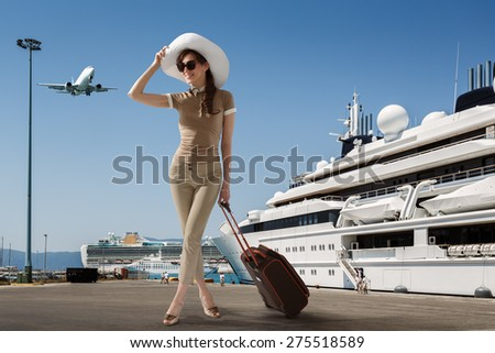 Stylish slim woman wearing sunglasses and white hat standing in seaport near docked cruise ship while smiling and holding her luggage on a summer sunny day. Travel, vacation, adventure concept. - stock photo