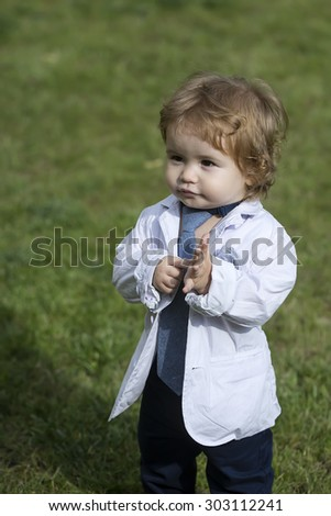 Stylish small baby boy with blond curly hair in white unbuttoned shirt grey necktie and trausers standing barefoot on fresh green grass lawn sunny day outdoor on natural background, vertical photo - stock photo