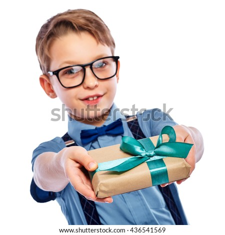 Stylish small boy in glasses giving a gift. He is smiling and looking in the camera. Isolated on a white background. - stock photo