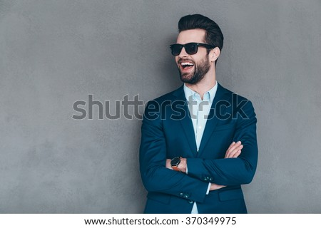 Stylish smile. Cheerful young handsome man in sunglasses keeping arms crossed and looking away with smile while standing against grey background - stock photo