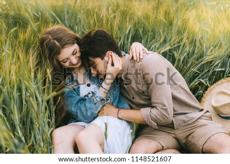 stylish smiling couple hugging in green grass, love story