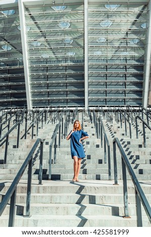 Stylish smiling red haired woman in fashionable blue dress walking on the summer city street near the glass business centre or stadium building. Cute fashion model in dress on the stairs. - stock photo