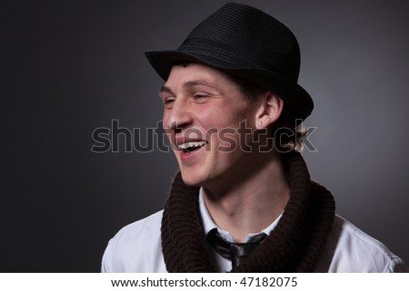 stylish smiling young man in black hat and brown scarf;