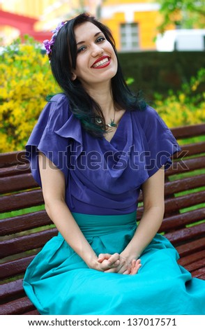 Stylish smiling young woman sitting on bench in park - stock photo