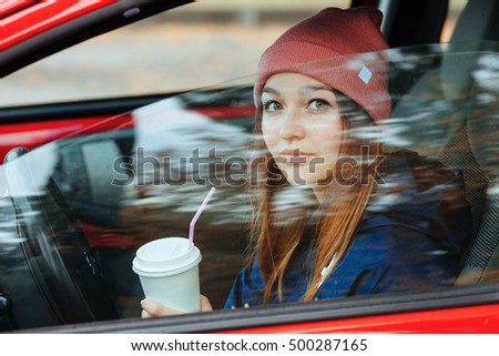 Stylish sporty brunette woman in trendy urban outwear driving a red car with big white disposable cup straw cold fall day Vintage filter film saturated color.