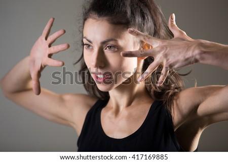 Stylish sporty young woman lifestyle portrait. Fit girl dancing. Happy caucasian female athlete posing. Studio image. Dark background - stock photo