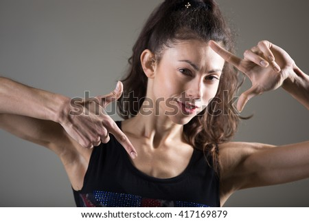 Stylish sporty young woman lifestyle portrait. Fit girl making frame with her hands. Happy playful caucasian female posing. Studio image. Dark background - stock photo