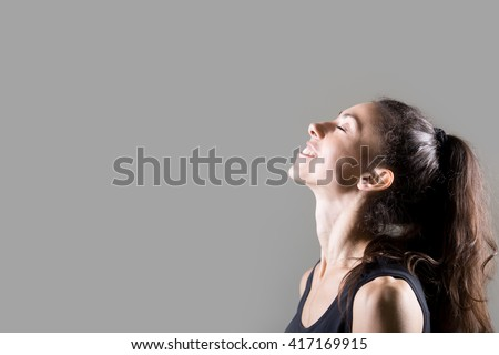 Stylish sporty young woman lifestyle portrait. Profile of fit girl breathing deep fresh air. Happy caucasian female dreaming with closed eyes and smiling. Studio image. Dark background - stock photo