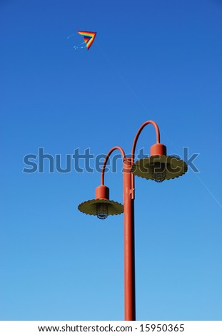 stylish street lamp with colorful kite and blue sky background