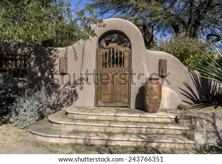 Stylish stucco rustic wood door archway entrance with steps to luxury home - stock photo
