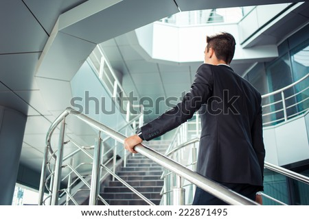 Stylish successful businessman goes up the stairs of the office building - stock photo