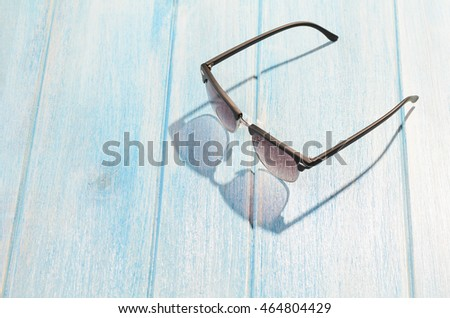 stylish sunglasses on blue wooden table with sunlight