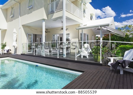 Stylish swimming pool with covered outdoor entertaining area - stock photo