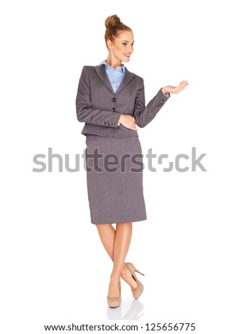 Stylish tall slender businesswoman in a classic grey suit standing holding out her empty palm for your product placement isolated on white - stock photo
