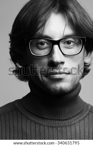 Stylish teacher, lecturer concept. Portrait of smiling young handsome man wearing eyeglasses over gray background. Trendy polo neck. Perfect long glossy hair. Yves Saint Laurent style. Indoor shot - stock photo