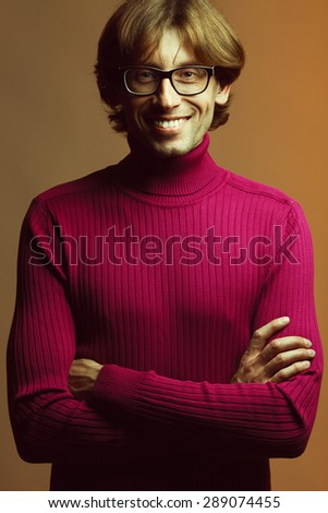 Stylish teacher, lecturer concept. Portrait of smiling young handsome man wearing fashion eyeglasses over orange background. Trendy plum colored polo neck. Perfect long glossy hair. Studio shot - stock photo