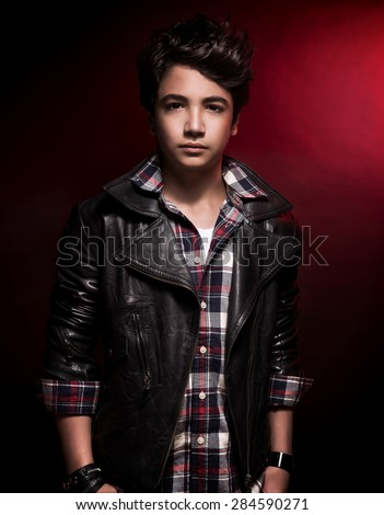 Stylish teen boy portrait over dark red background, handsome model wearing fashion shirt and leather jacket, funky adolescence style - stock photo