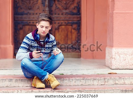 stylish teenage boy listens to the music on smart phone - stock photo