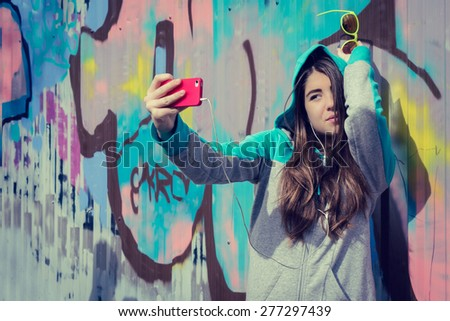 Stylish teenage girl in colorful sunglasses posing near graffiti wall and  taking self portrait with mobile phone - stock photo