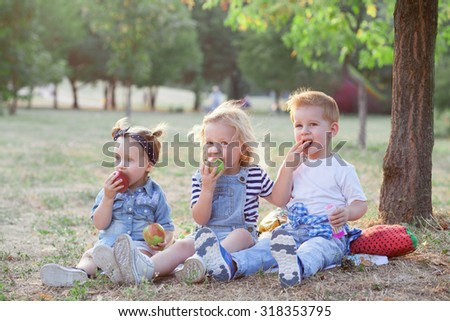stylish toddlers eating an apples during picnic - stock photo
