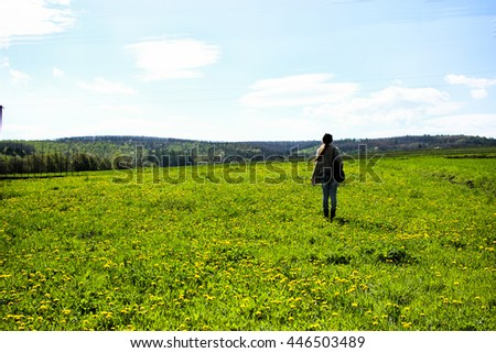 Stylish traveler girl in woolen gypsy hipster clothes and backpack hiking in spring dandelion field