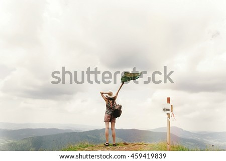stylish traveler hipster woman  with backpack holding map into sky on top of mountains , travel concept, space for text, back view - stock photo