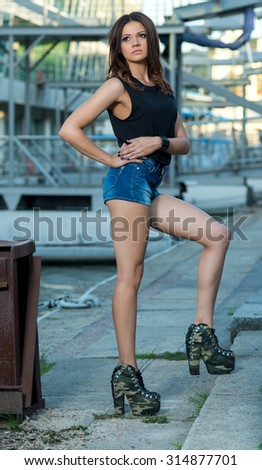 Stylish trendy attractive girl on the street. Fashion posing on the street. Magazine photographing. Fashion image of a woman. Fashion concept - stock photo