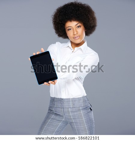 Stylish trendy beautiful African American woman showing a tablet computer holding the blank screen towards the viewer - stock photo