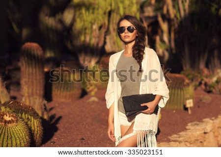 Stylish trendy beautiful girl with long braid posing in t-shirt and shorts with handbag against cactuses. Outdoor summer portrait - stock photo