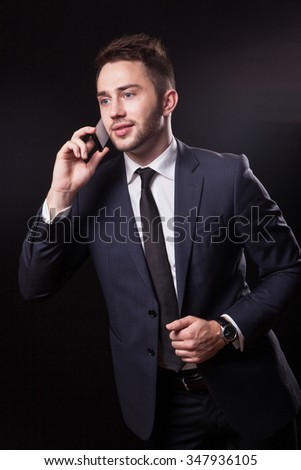 stylish, trendy businessman in a business suit on a black background talking on the phone and looking confidently at the camera. - stock photo