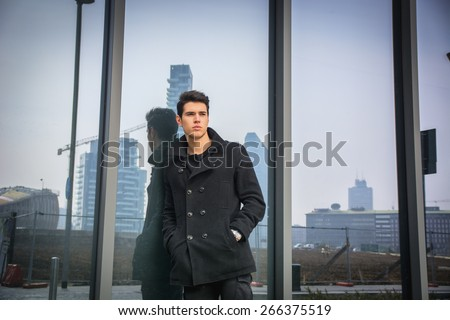 Stylish trendy young man standing outdoor against office window, looking confindent away