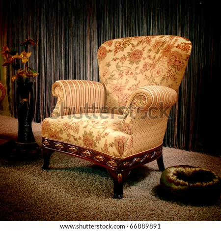 Stylish vintage armchair with pillow and flower in the vase
