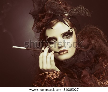 Stylish vintage lady in black and red silk smoking with cigarette holder