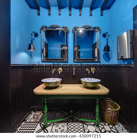 Stylish washroom in a restaurant. Upper part of the walls is blue, and lower part is dark-wooden. On the back wall there are two mirrors, two black lamps on the sides of mirrors and a wooden table