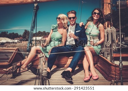 Stylish wealthy friends having fun on a luxury yacht  - stock photo