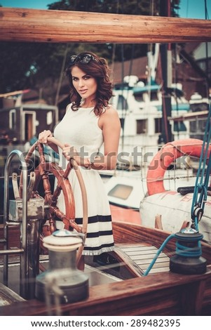 Stylish wealthy woman on a luxury wooden regatta