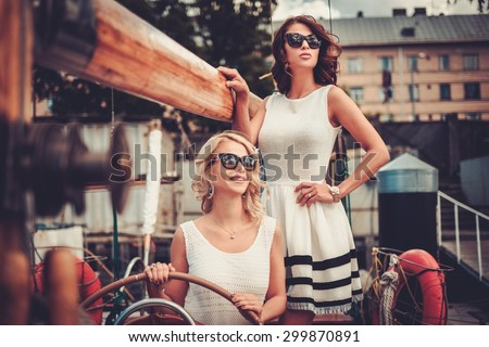 Stylish wealthy women on a luxury yacht  - stock photo