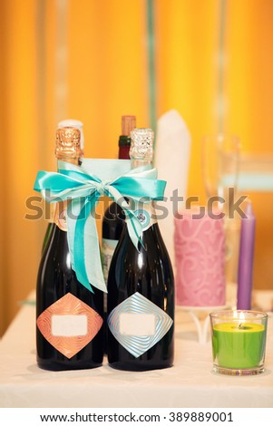 stylish wedding bottles of champagne on a holiday table and color candles
