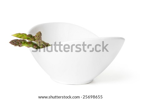 Stylish white bowl with asparagus spears.  Isolated on white, high key effect. - stock photo