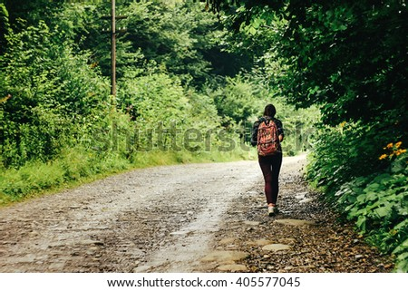 stylish woman hipster traveler walking on the road with backpack among trees on background of woods - stock photo
