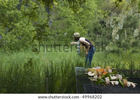 Stylish woman hosts BBQ with the green spring background - stock photo
