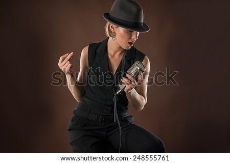 stylish woman in a hat with a retro microphone - stock photo
