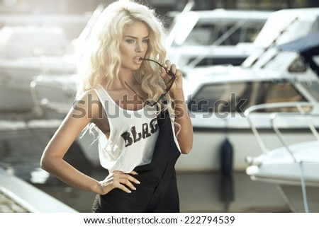 Stylish woman in dungarees standing on marina  - stock photo