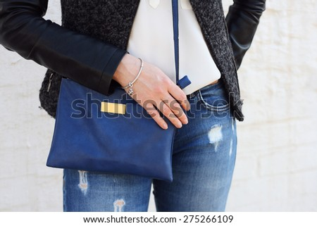 Stylish woman in jeans with small blue handbag clutch. fashion concept. - stock photo