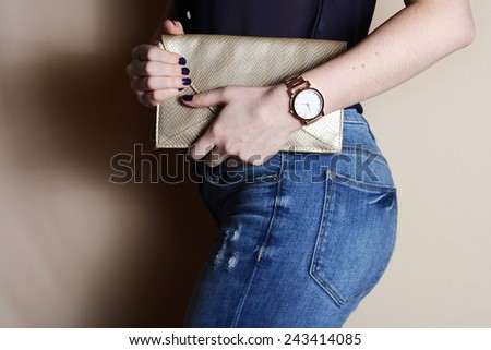 Stylish woman in jeans with small gold clutch and watch . fashion concept.
