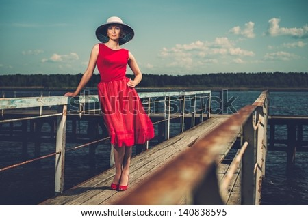 Stylish woman in white hat and red dress standing on old wooden pier - stock photo