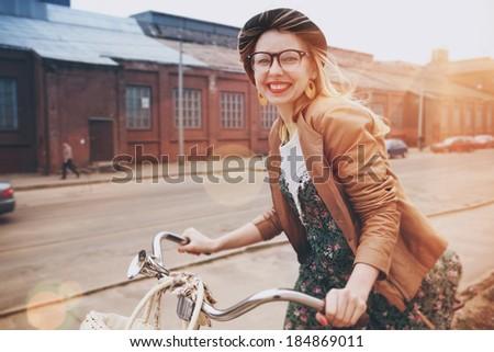 stylish woman riding on bike in morning sunshine - stock photo